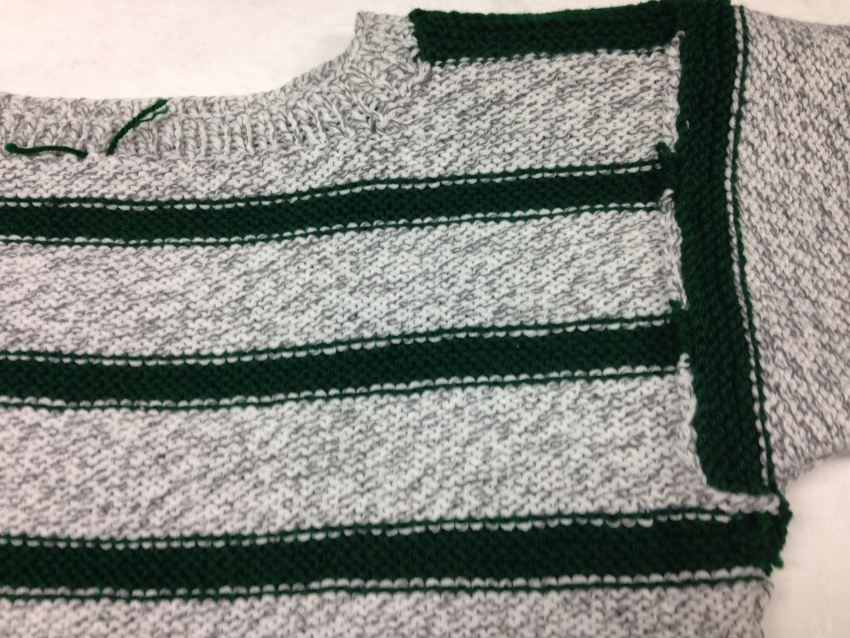 Photo of the inside body and the upper sleeve of the sweater showing the yarn ends woven in.