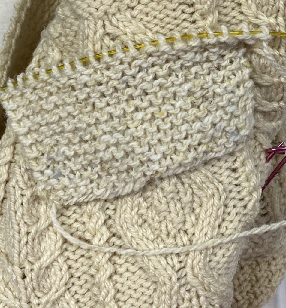 A knitted garter stitch swatch laid over the sweater.