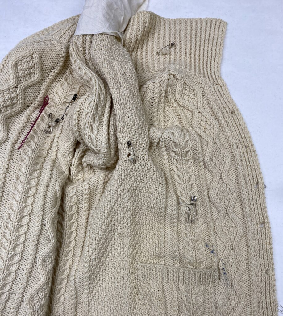 Photo A cable-knit cardigan sweater in un-dyed cream wool with damaged areas marked with safety pins.
