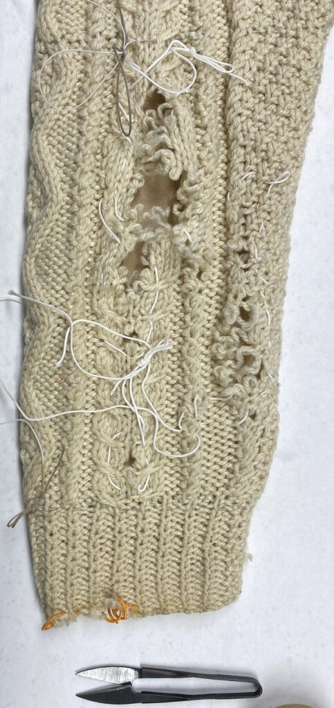 Cabled cardigan sweater sleeve showing extensive damage