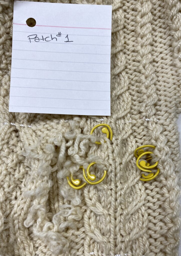 Photo showing a large hole in the sleeve of the cardigan and several broken stitches secured with yellow stitch markers.