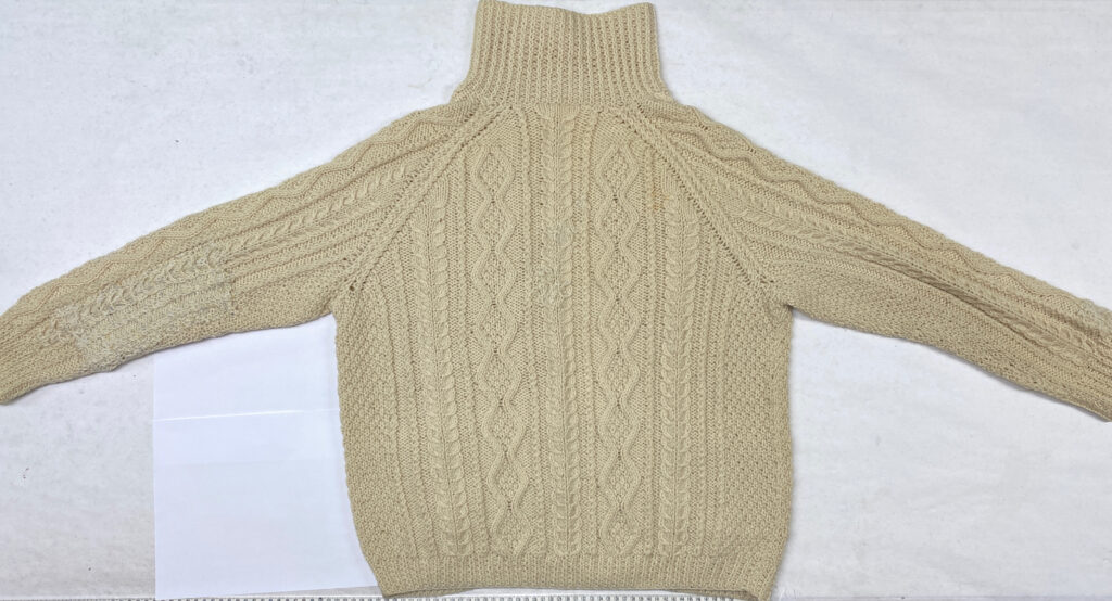 Cable sweater spread out to show the back repairs after blocking.