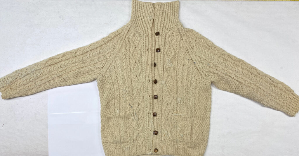 Cable sweater front spread out to show repairs after blocking.
