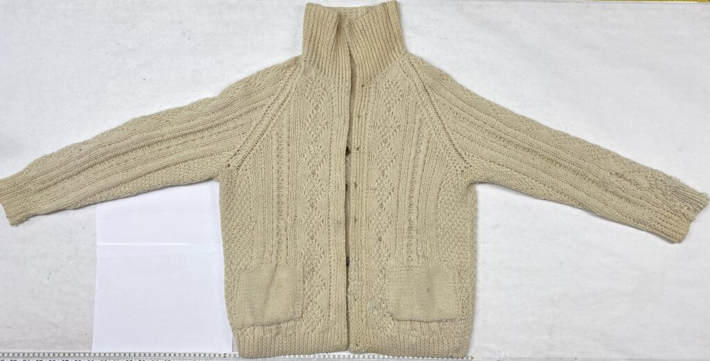 Cable sweater inside-out and spread out to show repairs after blocking.